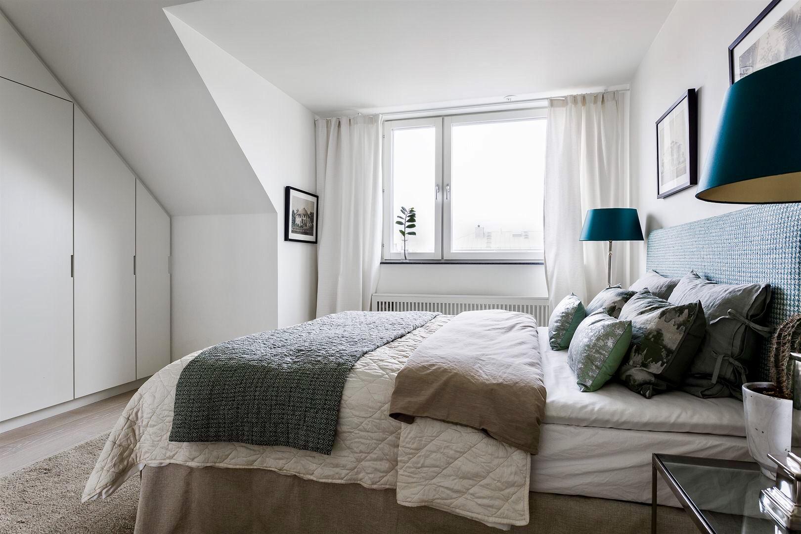 мансарда спальня кровать текстиль подушки встроенный шкаф прикроватные столики лампы окно