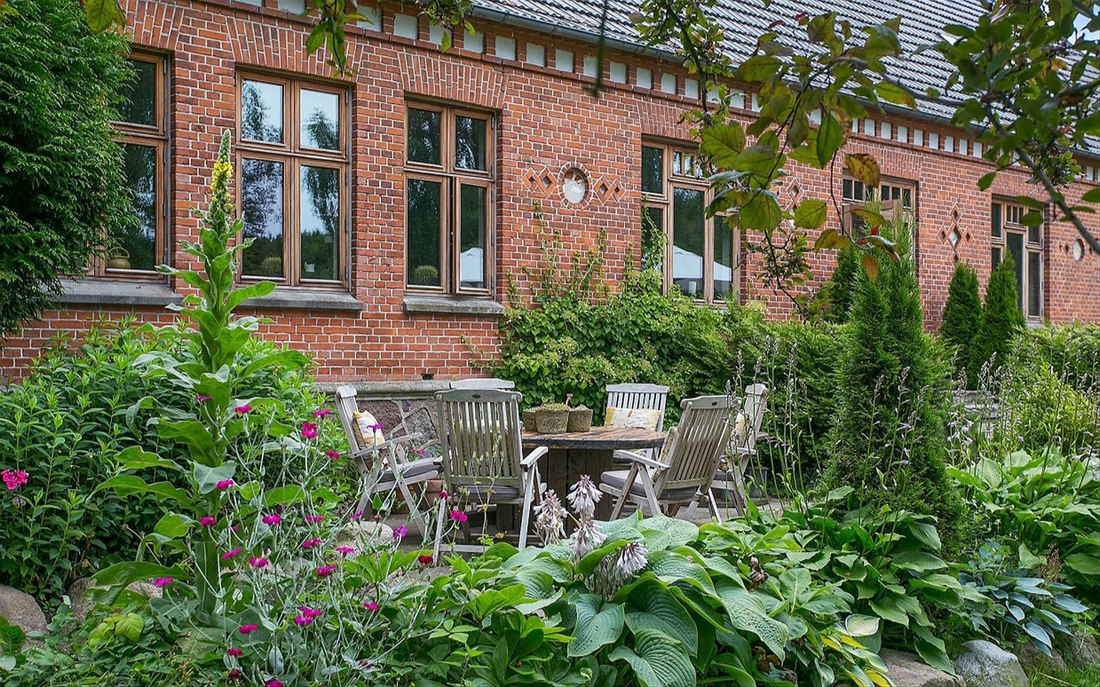 кирпичный фасад окна загородный дом кровля клумбы растения кустарники