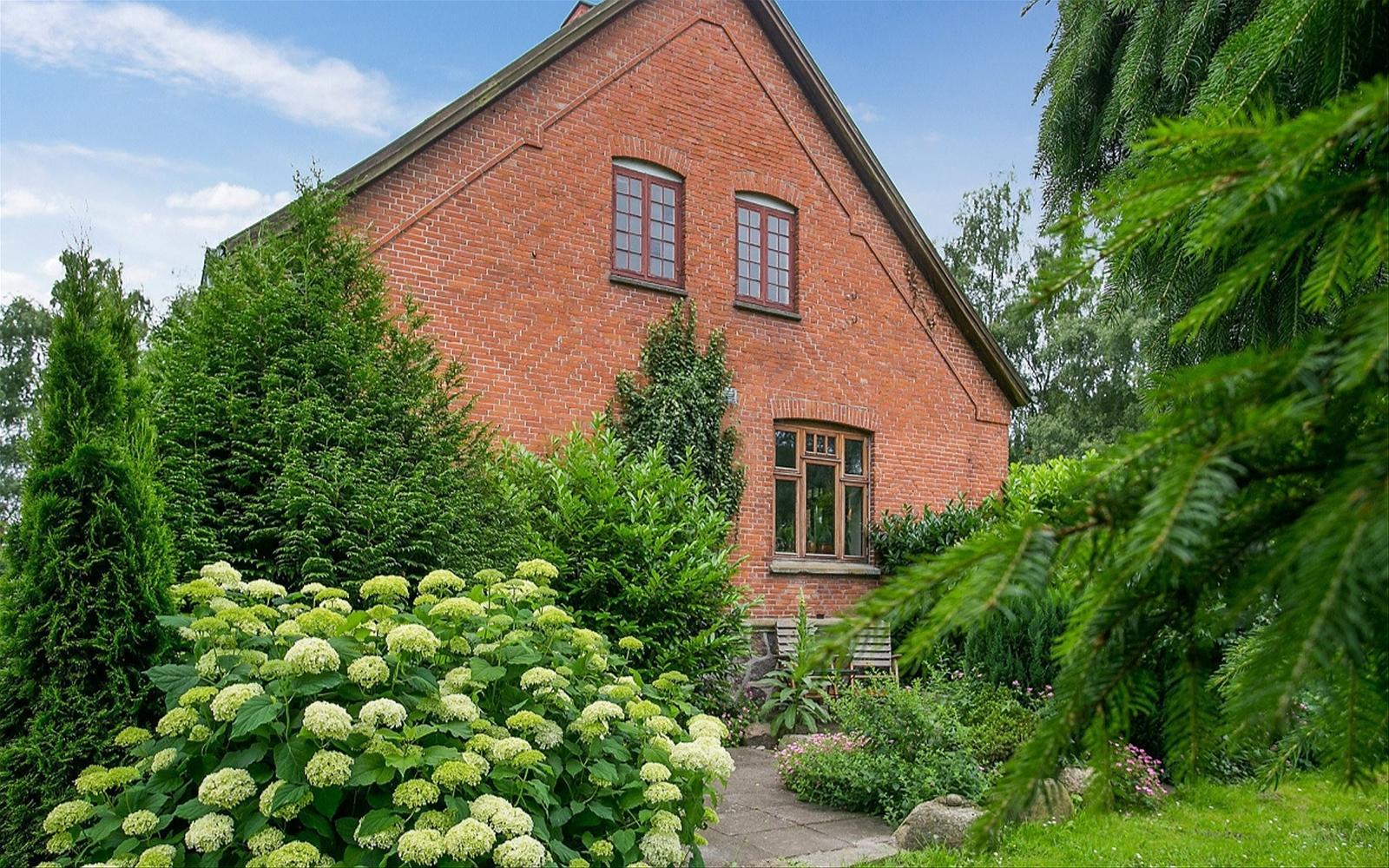 кирпичный дом кустарники клумбы цветы