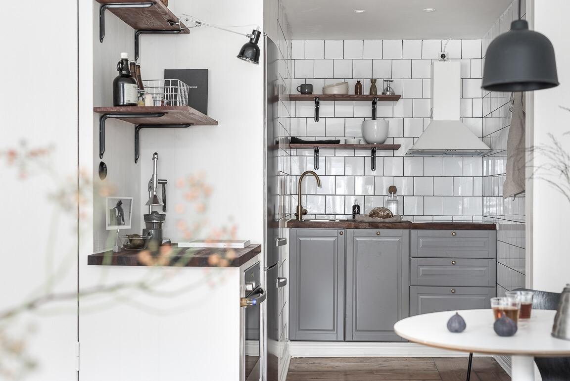 кухня белая квадратная плитка серые кухонные фасады варочная панель духовка