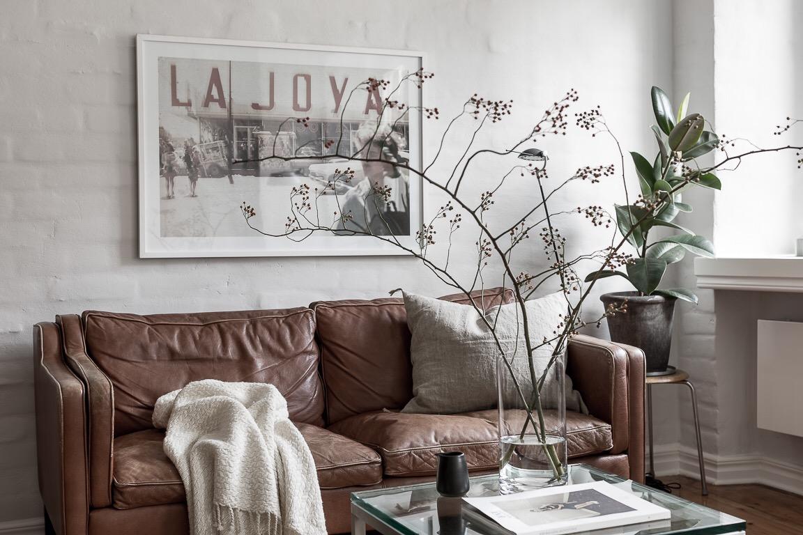кожаный диван постер на стене журнальный столик ваза