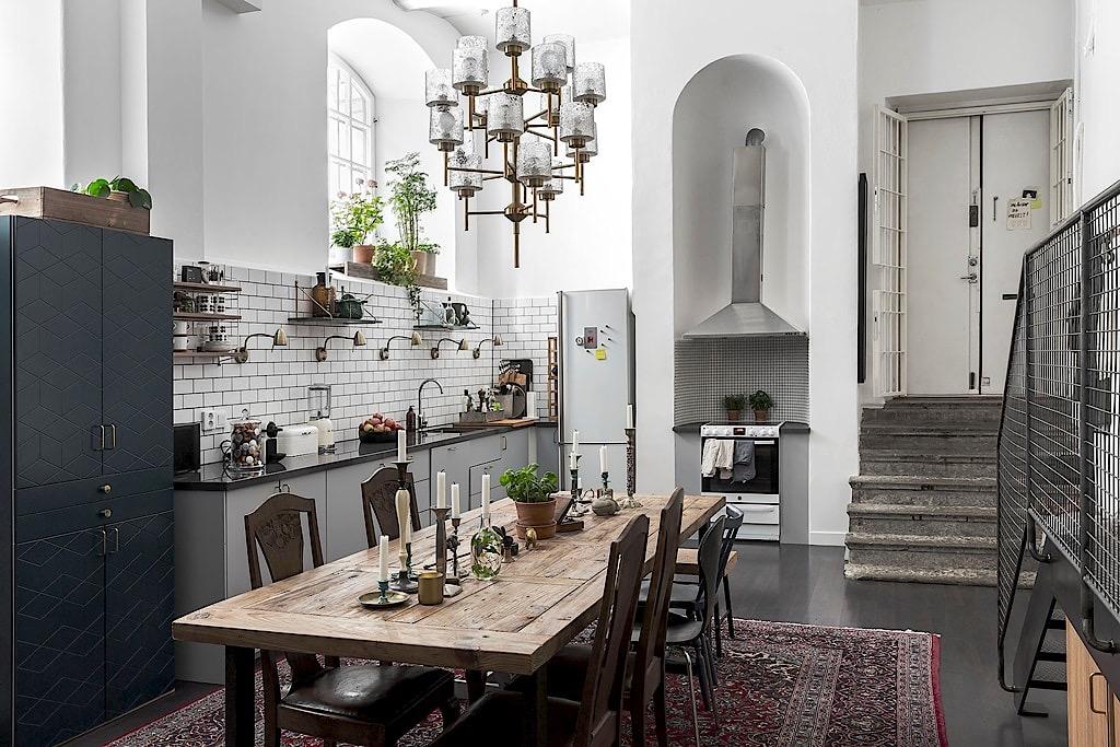 высокий потолок кухня белые стены темный пол стол ковер лестница кухонная мебель