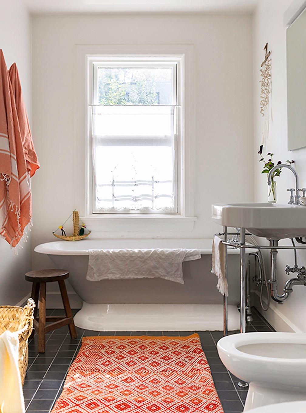 ванная комната окно ванна раковина унитаз корзина коврик черная плитка