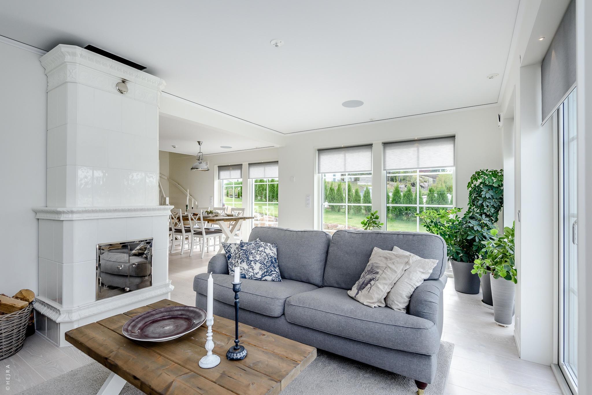 гостиная серый диван столик израсцовая печь комнатные растения корзина дрова