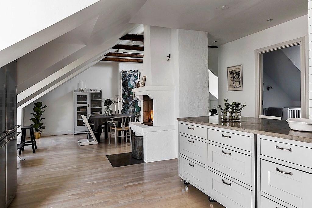 мансарда балки кухонная мебель ящики столешница мрамор камин гостиная обеденный стол