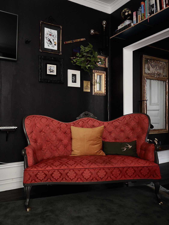 черные стены красный диван высокий белый плинтус