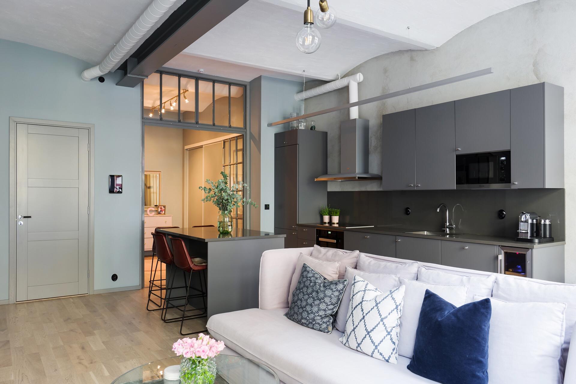 гостиная кухня перегородка стекло диван кухонный остров барные стулья