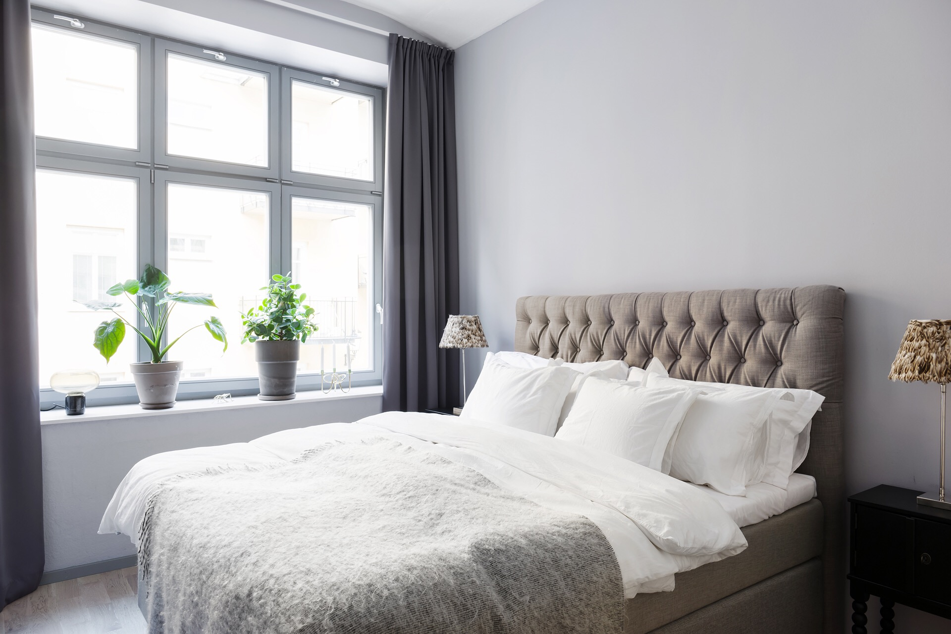 спальня кровать изголовье с утяжками текстиль подушки прикроватные тумбы лампы окно подоконник цветок