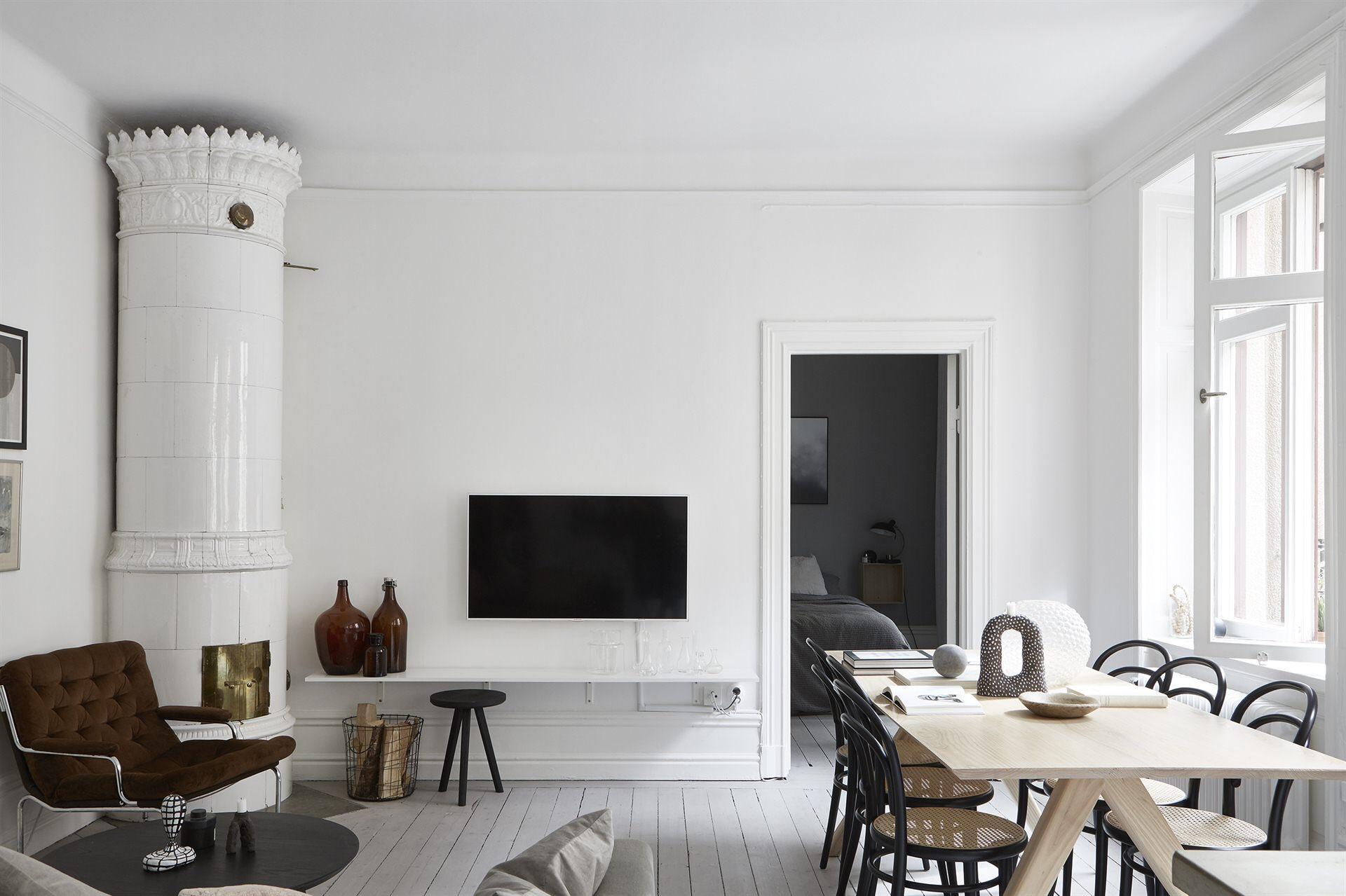 гостиная диван кресло консоль телевизор печь стол стулья белые стены сосновая доска