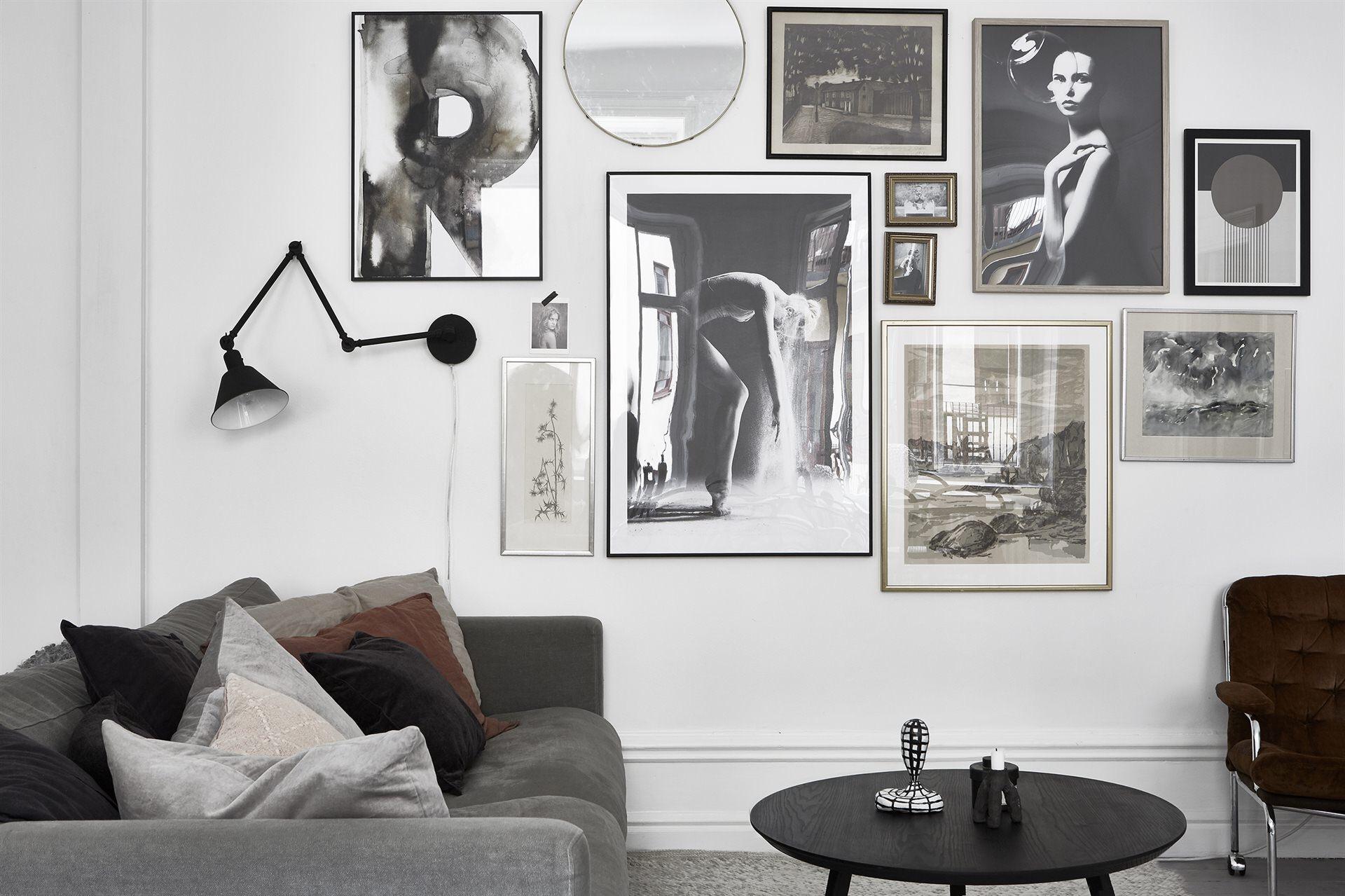серый диван подушки круглый столик белые стены картины рамы постеры настенный светильник