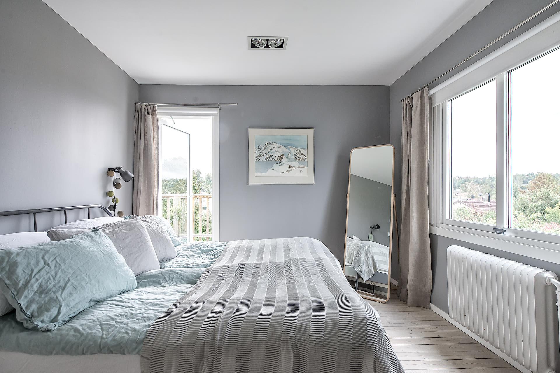 спальня серые стены кровать текстиль подушки окно напольное зеркало дверь на балкон
