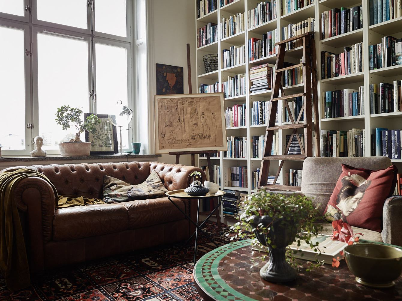 библиотека кожаный диван с утяжками книжный стеллаж мольберт лесенка окно