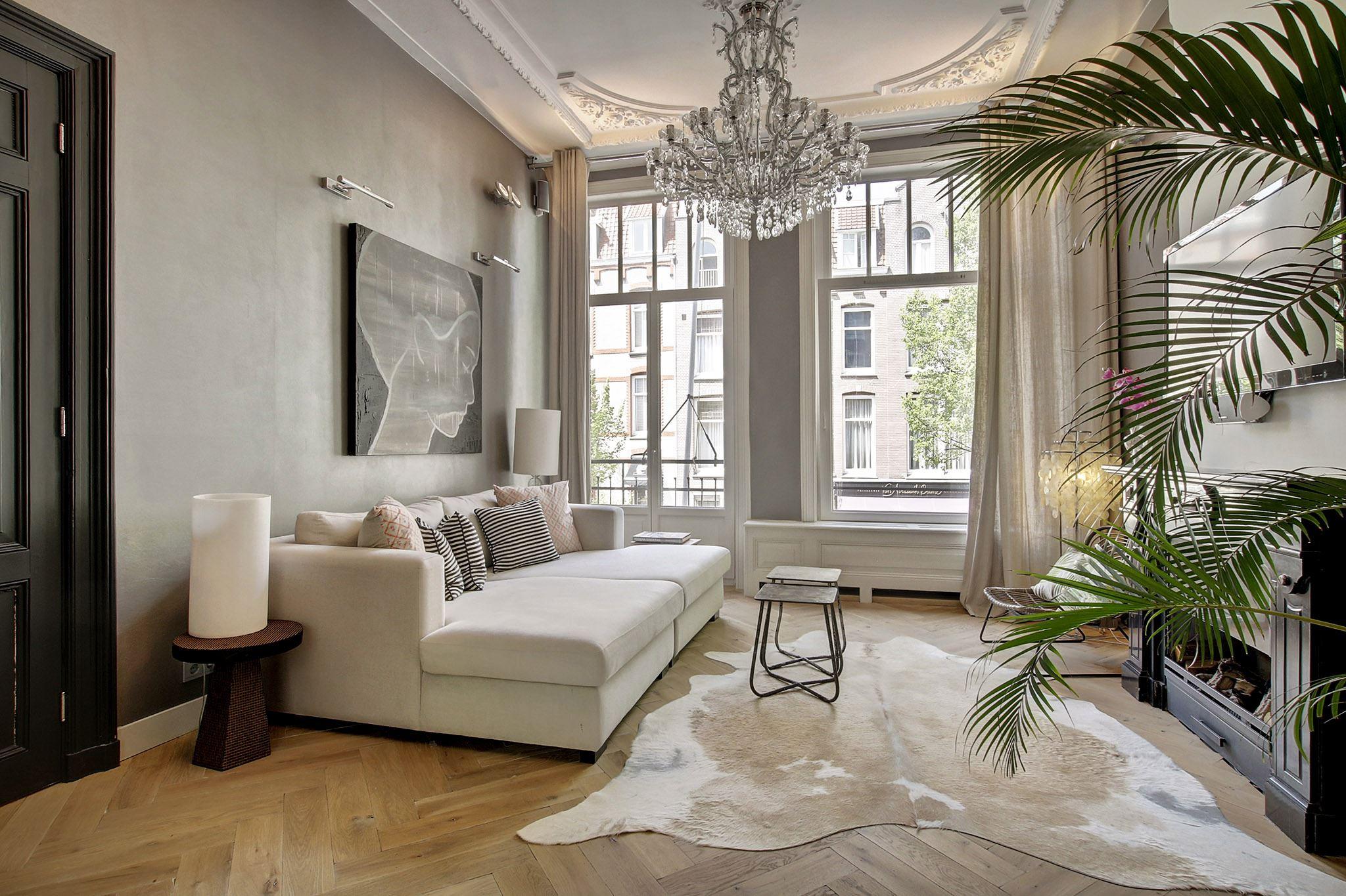 серые стены светлый паркет елочка камин большие окна лепнина бежевый диван подушки