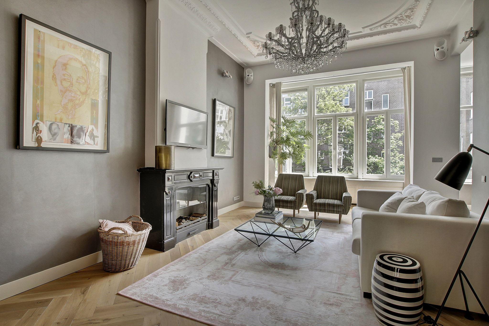 серые стены паркет бежевый диван кресла стеклянный столик камин телевизор корзина лепнина
