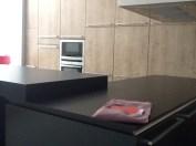 Una gran cocina panelada en madera y negro. Las grandes dimensiones de esta cocina pide atrezzo en gran formato: tablas de cortar, grandes cacerolas...