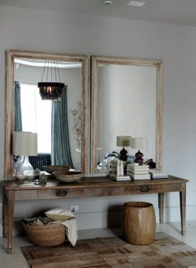 A pair of antique mirrors hangs over a vintage farm table in the library area.