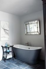 An antique mirror hangs over the freestanding tub.