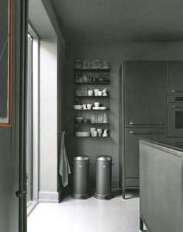 Los icónicos cubos de basura que lanzaron la firma Vipp al estrellato, descansan bajo una estantería con menaje también de Vipp.