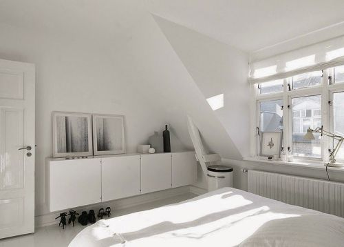 En la habitación principal, un contenedor alargado de PO Inventar funciona como cómoda. La cama es de Hästens y la lámpara de Fontana Arte. Hasta las fotografías de Anders Hviid juegan al binomio blanco y toque negro.
