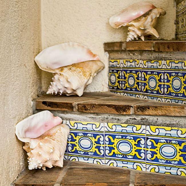 Μια σκάλα με ethnic-coastal και πλακάκια ζωγραφισμένα στο χέρι.