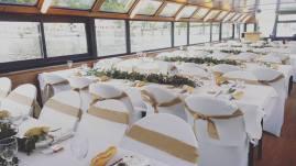 Décoration champêtre d'une péniche avec installation de housses et noeuds de chaise jute, décoration des tables avec guirlandes de feuillage.