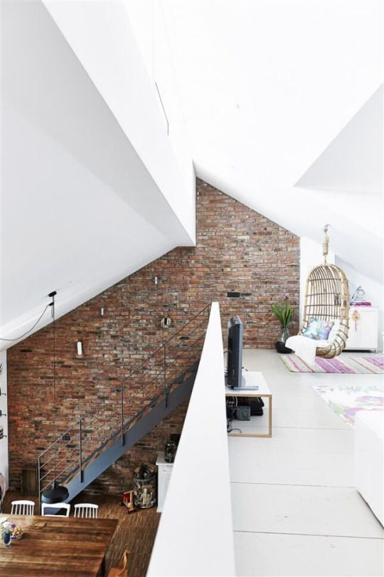 Frankfort, Germany | Built from a recycled barn, one entire side of the house is built from the old barn brick, each of which have been washed with a brush. Beams have been recycled as structural support for the mezzanine where there's a family room (with a lovely wicker swing!) and study. Love the stairs and the multi-angled ceiling as well.: