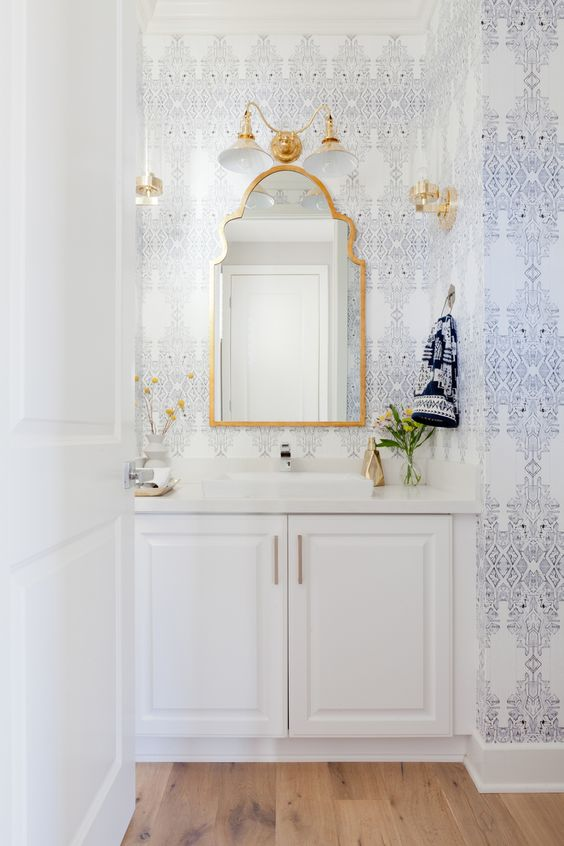 Elegant printed wallpaper in blue and white with gold accents and mirror above the sink with white bathroom cabinets. Stunning bathroom design idea!:
