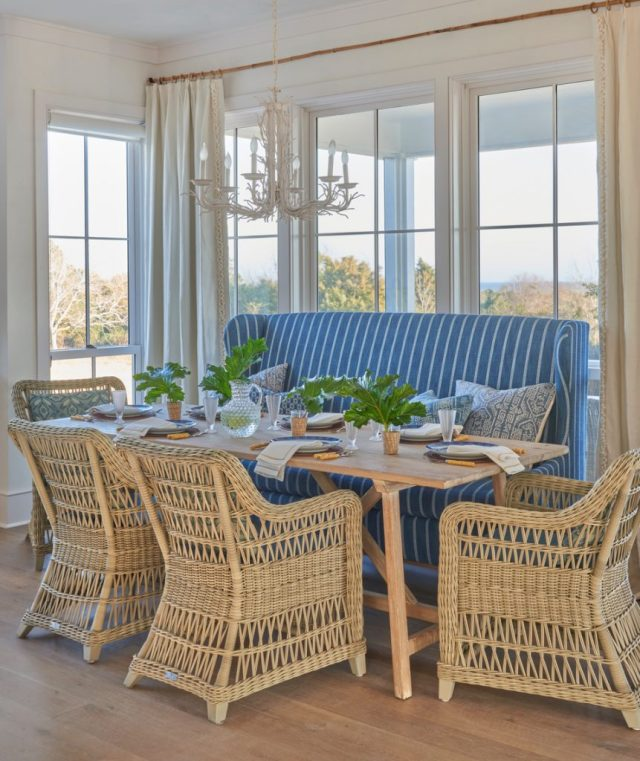 Woven chairs and table with big windows in the background