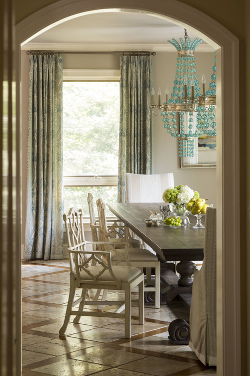 Look from hall into dining room with table, chairs and big window with curtains