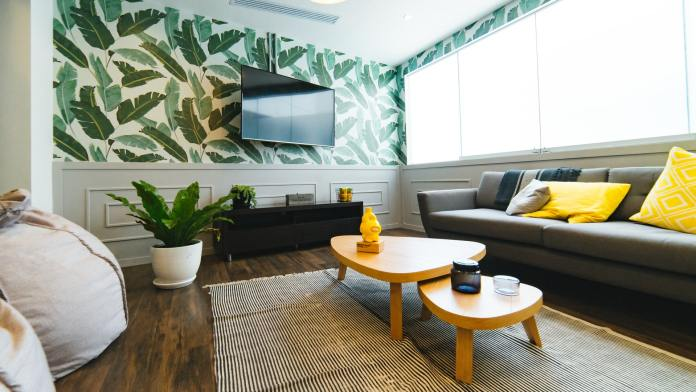 Living room with coffee table, couch and TV on the wall