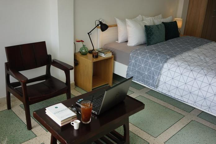 College dorm room with bed, bedside table with a lamp and a small table with laptop and chair