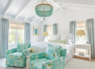 White and blue designed bedroom with king size bed, chandelier and two armchairs in front of the bed