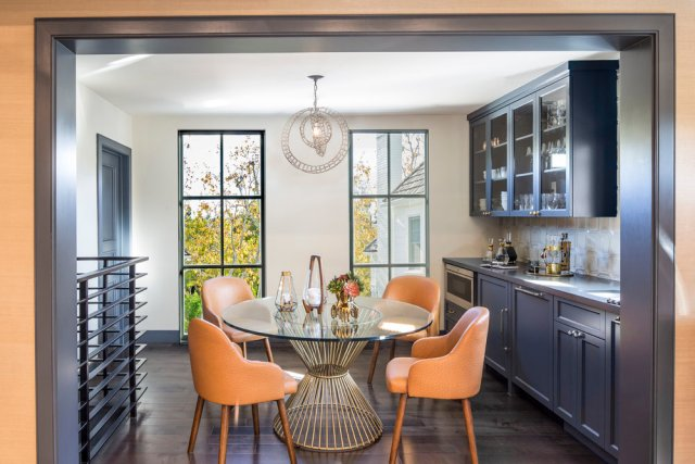 Kitchen with round glass table and orange chairs