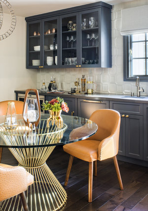 Kitchen with gray kitchen elements, round table and orange chairs