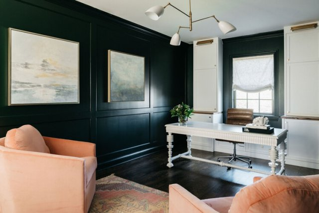 Home office with black wall and white table
