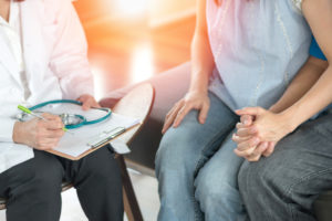 couple holding hands while speaking with an infertility doctor