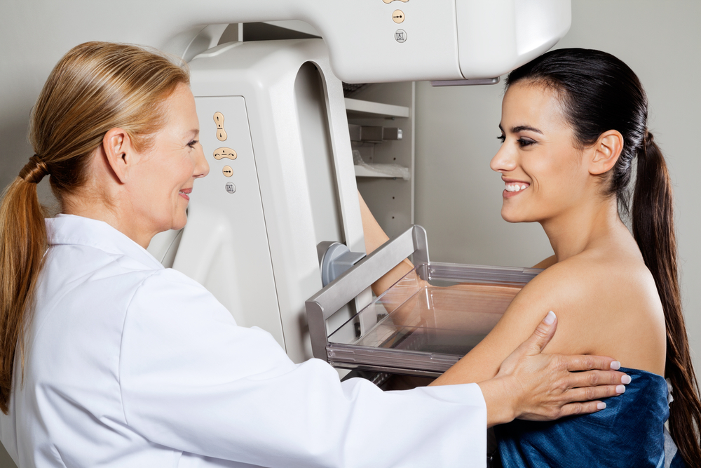 Mature female doctor assisting young patient during mammogram x-ray test