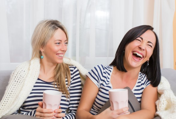 Two happy women laughing while sitting in bed at home