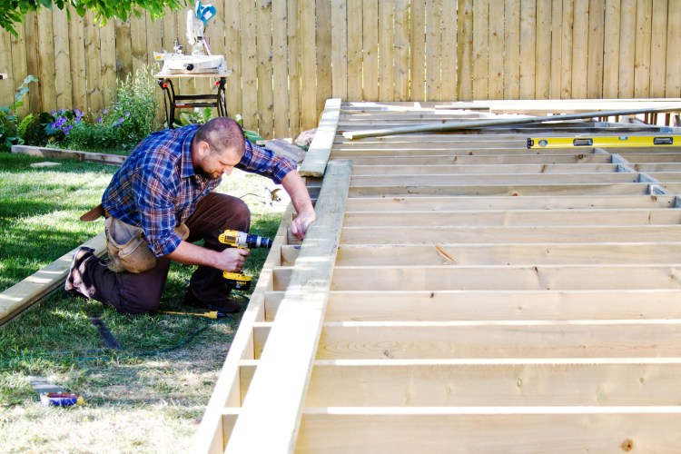Carpenter drilling on deck plank