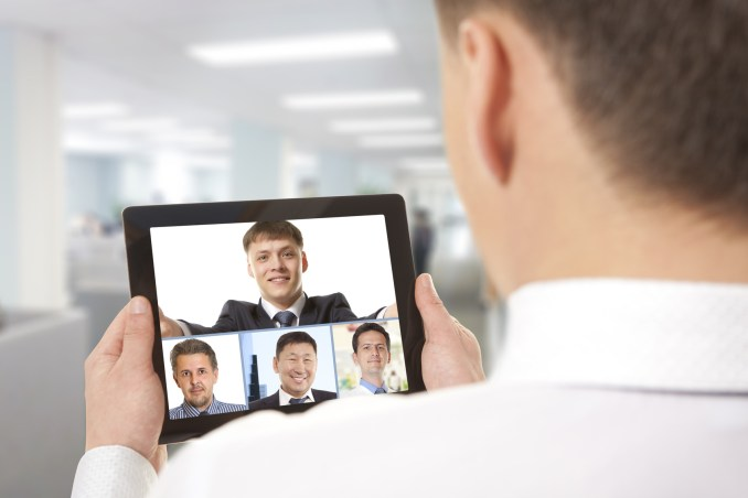 Cropped image of team businessman attending video conference with colleague on digital tablet