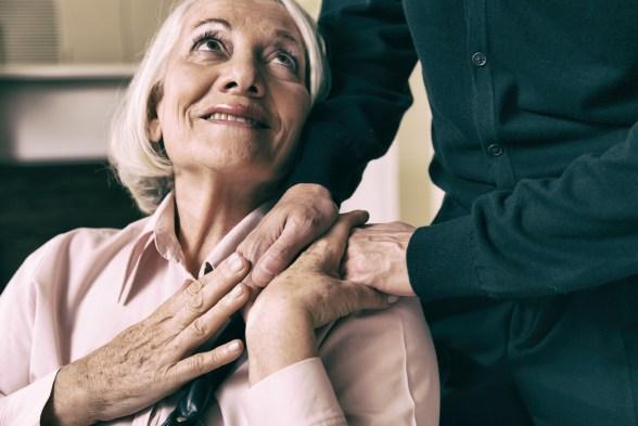 Senior woman on wheelchair taking her husband's hand.