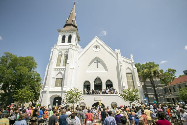 People stand outside as parishioners leave the Emanuel A.M.E. Church, Sunday, June 21, 2015, in Charleston, S.C., four days after a mass shooting at the church claimed the lives of its pastor and eight others. (AP Photo/Stephen B. Morton)