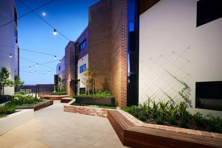 LIV Apartments garden along tall walls