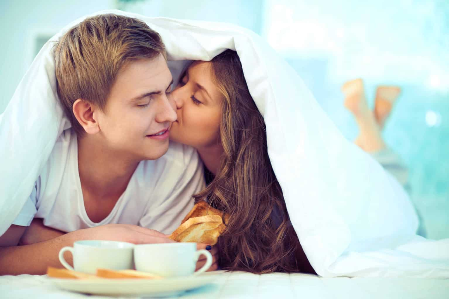 Couple enjoying one another while having breakfast in bed