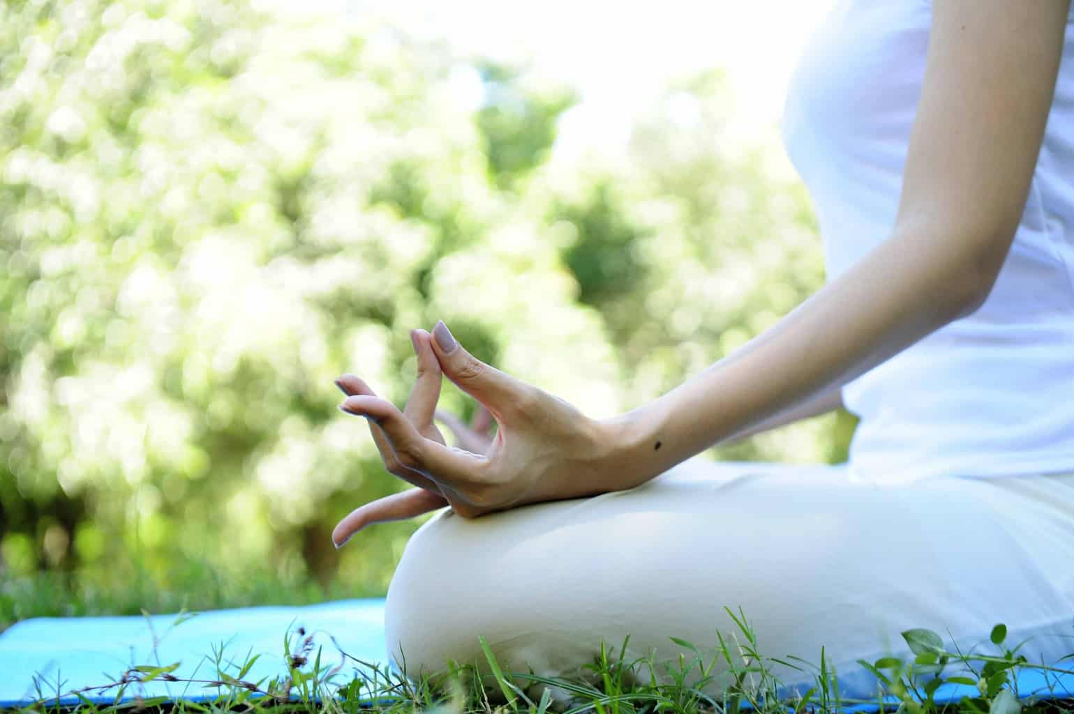 Woman wears white doing meditation in the park