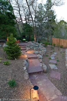 Locally harvested Chocolate Flagstone walkway and steps illuminated at dusk by low voltage lighting.