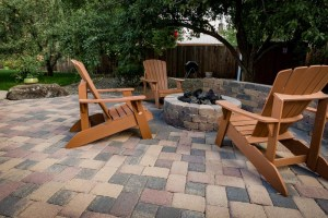 Paver patio and seat wall surrounding natural gas firepit with turf area in background