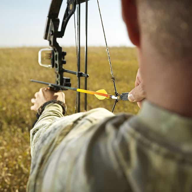 Bow hunter in field pulling back arrow on compund bow.