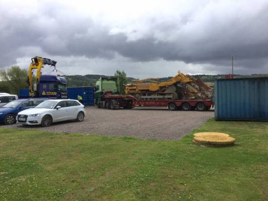 Busy car park with Drainage heavy machinery arriving and containers being moved.