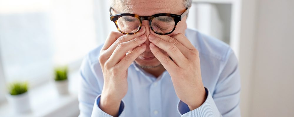 A man wearing glasses, rubbing his eyes in the office
